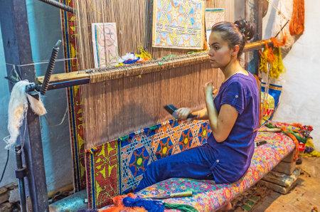 machine made: KHIVA, UZBEKISTAN - MAY 3, 2015: The teenage girl weaves the traditional Uzbek rug in the workshop, on May 3 in Khiva. Editorial