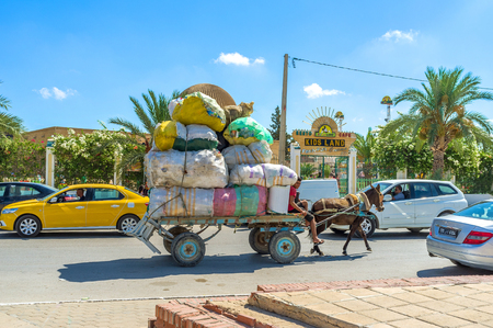 trafic: KAIROUAN, TUNISIA - AUGUST 30, 2015: The laden horse cart with the numerous lerge bags of plastic garbage, on August 30 in Kairouan.