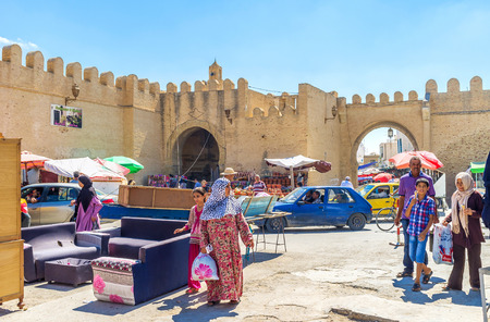 kairouan: KAIROUAN, TUNISIA - AUGUST 30, 2015: The crowded street market next to the medieval citadel walls of Medina, on August 30 in Kairouan.