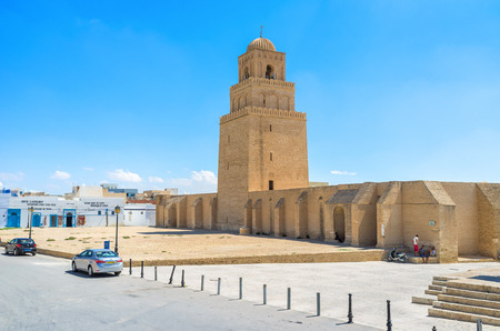 kairouan: KAIROUAN, TUNISIA - AUGUST 30, 2015: The medieval Grand Mosque looks like the defensive fortress with a high ramparts, huge minaret and large courtyard, on August 30 in Kairouan.