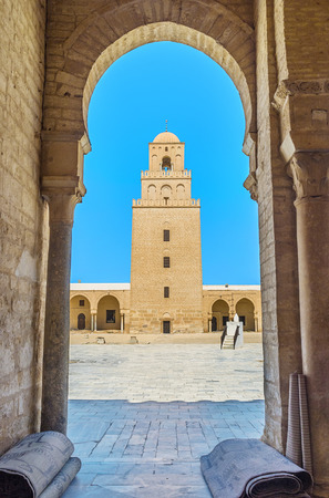 kairouan: The view on the old Minaret of the Grand Mosque through the arch of its courtyard, Kairouan, Tunisia.