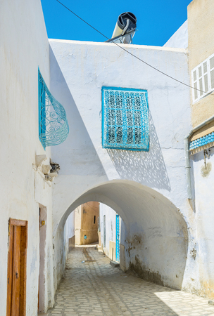 kairouan: The low passage under the old house on the narrow street of Kairouan Medina, Tunisia.
