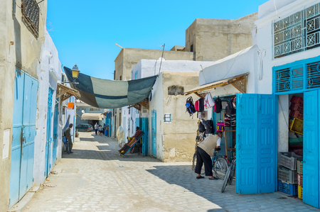 kairouan: KAIROUAN, TUNISIA - AUGUST 30, 2015: The working neighborhood of Medina with the stalls, old weaving workshops and draperies, on August 30 in Kairouan.