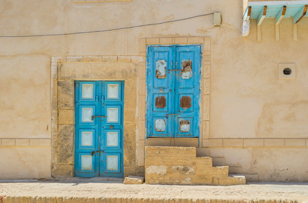 kairouan: The wall of the old house in Medina with two bright blue doors, Kairouan, Tunisia. Stock Photo