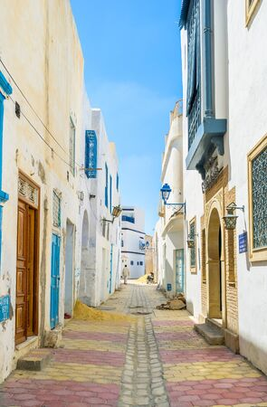 kairouan: KAIROUAN, TUNISIA - AUGUST 30, 2015: The narrow street of Medina is very clean and all the houses are restored, on August 30 in Kairouan.