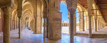 kairouan: KAIROUAN, TUNISIA - AUGUST 30, 2015: The medieval shady covered terrace of the Grand Mosque consists of many raws of columns that support the arches and ceiling, on August 30 in Kairouan.