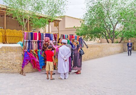headcloth: KHIVA, UZBEKISTAN - MAY 3, 2015: The members of Uzbek family in traditional costumes choose the headclothes at the market stall, on May 3 in Khiva.
