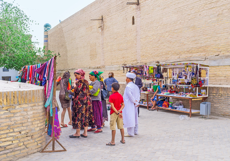 headcloth: KHIVA, UZBEKISTAN - MAY 3, 2015: The Uzbek family in traditional costumes choose the gifts at market stall, on May 3 in Khiva.