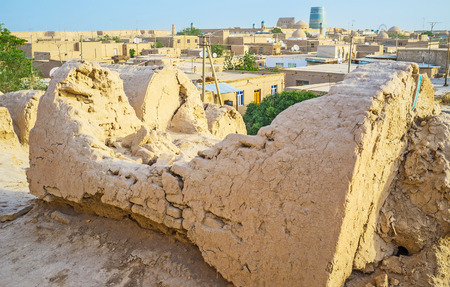 rampart: The ruins of the ancient clay tomb on the rampart of Khiva fortification with the view on the town roofs on the background, Uzbekistan.