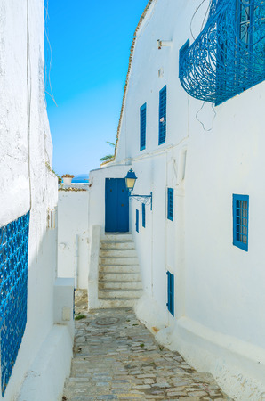 backstreet: The narrow backstreet with bright blue sky and narrow strip of the sea on the background, Sidi Bou Said, Tunisia.