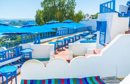 sidi bou said: SIDI BOU SAID, TUNISIA - AUGUST 31, 2015: The fine outdoor restaurant on the mountain slope is very popular among tourists, visiting the Northern Tunisia, on August 31 in Sidi Bou Said.