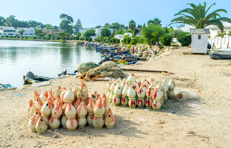 september 2: CARTHAGE, TUNISIA - SEPTEMBER 2, 2015: The earthenware pots for catching octopuses on embankment of the fishing harbor, on September 2 in Carthage.