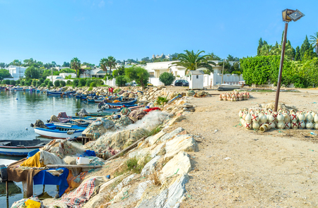 september 2: CARTHAGE, TUNISIA - SEPTEMBER 2, 2015: The ancient Punic port nowadays became the village fishing harbor with many colorful boats and clay pots for octopus on the bank, on September 2 in Carthage.