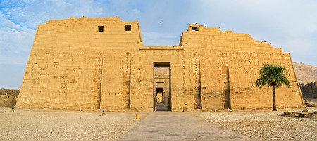 eligion: The massive facade of the Mortuary Temple of Ramesses III, located at archaeological site, named Medinet Habu, Luxor, Egypt.