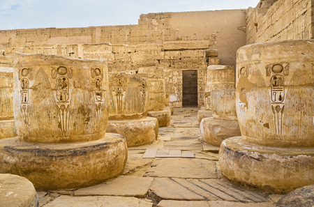 eligion: Many rows of the ruined columns, decorated with Egyptian hieroglyphs, Habu Temple, Luxor.
