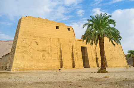 eligion: The scenic facade of the Habu Temple with the beautiful palm in front of it, Luxor, Egypt.
