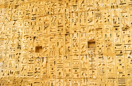 eligion: The stone wall in Habu Temple covered with thousands of the ancient hieroglyphs, Luxor, Egypt.