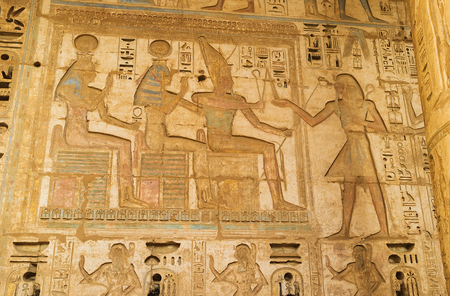 eligion: The dramatic scene of life of the ancient Egyptian Gods, carved on the stone wall of the Habu Temple, Luxor, Egypt.