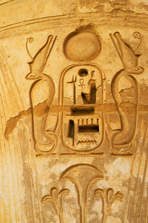eligion: The detail of the stone column in Habu Temple with the carved cobras around the Phraoh, Luxor, Egypt.