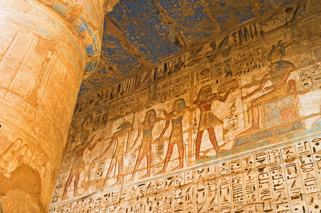 eligion: The traditional scenes from Egyptian mythology on the wall of Habu Temple, Luxor, Egypt.