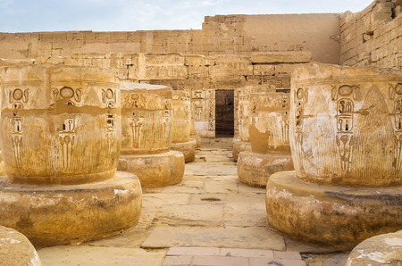 eligion: The hall of the ruined  ancient columns, carved with the sacred cobras and other symbols and hieroglyphs of Egyptian culture, Luxor.