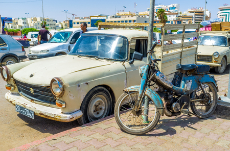 bab: SFAX, TUNISIA - SEPTEMBER 3, 2015: The old car and bike parked at the souq, located at Bab Jebli gates, on September 3 in Sfax. Editorial