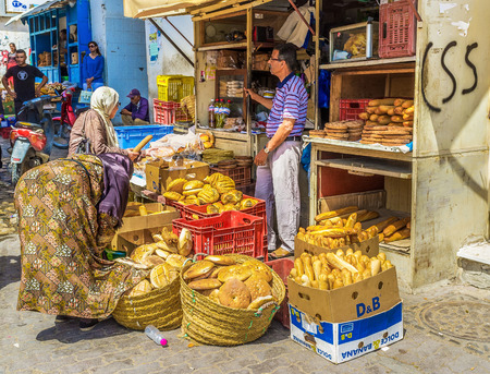 chose: SFAX, TUNISIA - SEPTEMBER 3, 2015: The locals chose the freshest bread in a market stall, on September 3 in Sfax.