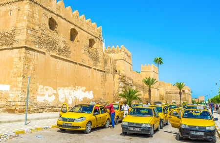 bab: SFAX, TUNISIA - SEPTEMBER 3, 2015: The large taxi stand next to the Bab El Kasbah Gates, the drivers clean their cars and wait for the clients, on September 3 in Sfax.