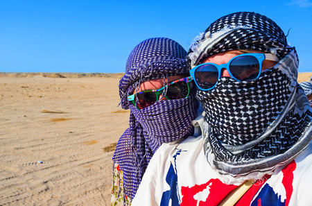 The portrait of young couple with faces, hiden under arabic scarves and sunglasses, during safari in Sahara desert, Hurghada, Egypt. Stock fotó