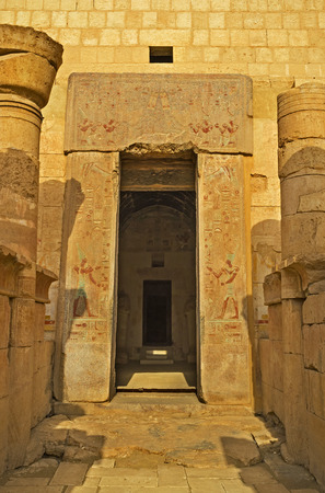 mortuary: The entrance to the Hatshepsut Temple with the stone door frame, decorated with the ancient frescoes, Luxor, Egypt.