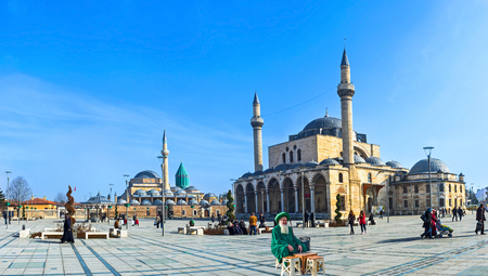 selimiye mosque: KONYA, TURKEY - JANUARY 20, 2015: The local man in green traditional costume on the central square with the Mevlana Museum  and Selimiye Mosque on the background, on January 20 in Konya.