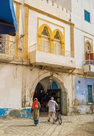 separates: SOUSSE, TUNISIA - SEPTEMBER 6, 2015: The old mansion with the pass through it separates two parts of the local market, on September 6 in Sousse.