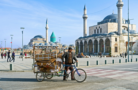 KONYA, TURKEY - JANUARY 20, 2015: The man transporting the garbage in cargo cycle through the central square of the old town, on January 20 in Konya.