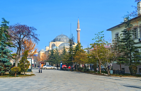 konya: KONYA, TURKEY - JANUARY 20, 2015: The green park and the black dome and high minaret of the Serafeddin mosque on the background, on January 20 in Konya.