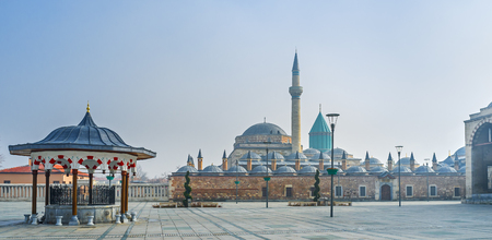 The panoramic view of the Mevlana Museum in light morning haze with the beautiful ablution fountain on the foreground, Konya, Turkey. 新闻类图片