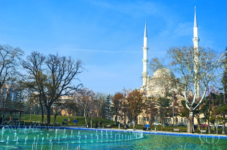 konya: KONYA, TURKEY - JANUARY 20, 2015: The view on great Haciveyiszade Mosque, hiden behind the trees with the large fountain on the background, on January 20 in Konya.