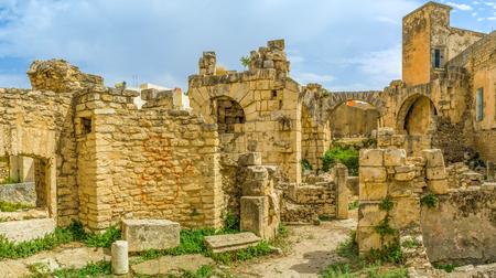 arcos de piedra: Las paredes y arcos de piedra y unas pocas de las columnas en ruinas son las �nicas partes conservadas de los ba�os romanos en El Kef, T�nez.