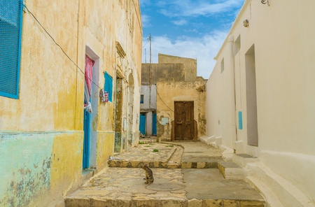 residential neighborhood: The small yard in old residential neighborhood of El Kef with crumbling walls and wooden doors, Tunisia.