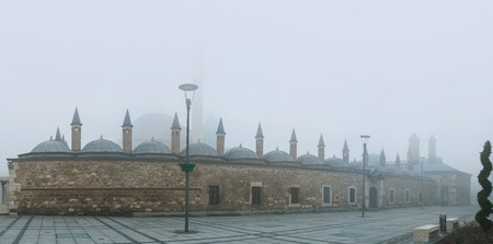 konya: The silhouette of Mevlana Museum is hidden under the hard winter mist, Konya, Turkey. Editorial