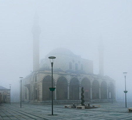 konya: The hard mist hides the beauty of Selimiye Mosque, showing only its silhouette, Konya, Turkey.