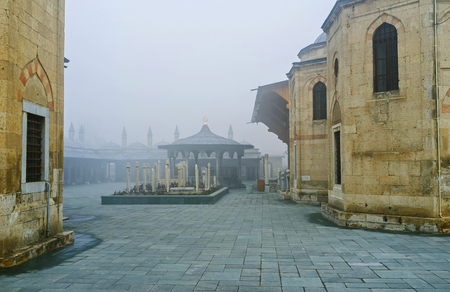 konya: The misty view on the courtyard of Mevlana Museum with the silhouette of its beautiful sadirvan and medieval dervish cemetery, Konya, Turkey.