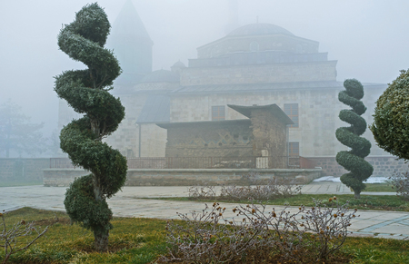 ornamental garden: The beautiful ornamental garden covered by frost, and the silhouette of Mevlana Museum on the background, Konya, Turkey.