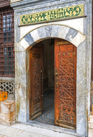 KONYA, TURKEY - JANUARY 20, 2015: The carved wooden door to the  Mevlana Mausoleum with the old arabic calligraphy over the entrance, on January 20 in Konya.