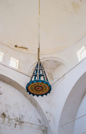 ethnographical: EL KEF, TUNISIA - SEPTEMBER 5, 2015: The wooden chandelier decorated with colorful islamic patterns located in building of the former mosque, serving as Ethnographic Museum, on September 5 in El Kef.