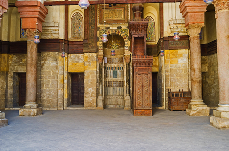 in ceiling: CAIRO, EGYPT - OCTOBER 10, 2014: The carved wooden minbar and stone mihrab of Qalawun mosque , on October 10 in Cairo.