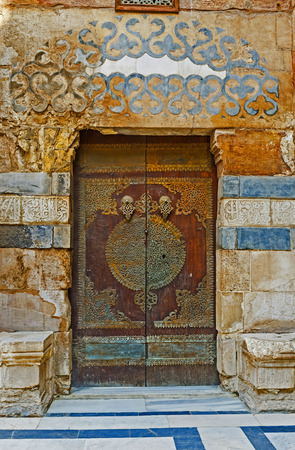 medievales: CAIRO, EGYPT - OCTOBER 10, 2014: The wooden door with the pattern of the metallic lace in Al-Nasir Muhammad complex, on October 10 in Cairo.