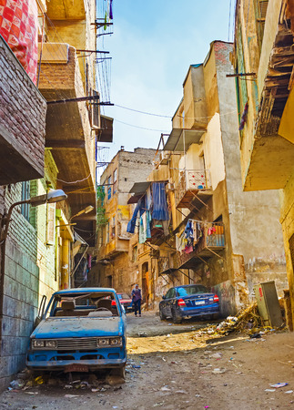 bab: CAIRO, EGYPT - OCTOBER 12, 2014: The dusty hilly street in Bab Al Khalq district with abandoned car on the foreground and the piles of garbage on the dirt road, on October 12 in Cairo.