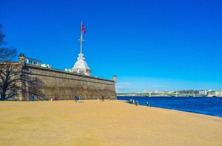 peterburg: SAINT PETERSBURG - APRIL 24, 2015: The beach of Neva River next to the Naryshkin Bastion of the Peter and Paul Fortress on Zayachy Island, on April 24 in Saint Petersburg.