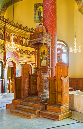 coptic orthodox: CAIRO, EGYPT - OCTOBER 12, 2014: The wooden thrones with the gilt iconostasis on the background in the prayer hall of Mar Jirjis (St George) church, on October 12 in Cairo. Editorial