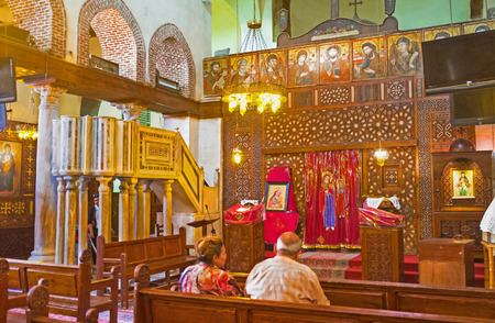 coptic orthodox: CAIRO, EGYPT - OCTOBER 12, 2014: The  prayer hall of St Barbara church with the wooden iconostsasis and the old stone amvon, on October 12 in Cairo.